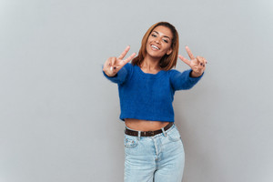 Young happy african woman in sweater and jeans showing peace and looking at camera. Isolated gray background