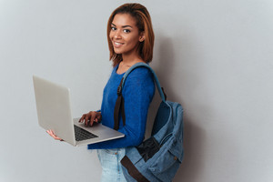 Young happy african woman in sweater and jeans with backpack holding laptop in hands standing sideways and looking at camera. Isolated gray background