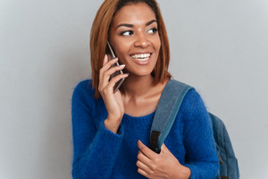 Young happy african woman in sweater with backpack talking at phone and looking aside. Isolated gray background