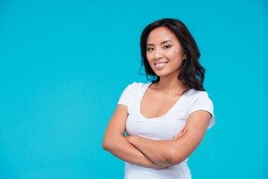 Young happy asian woman standing with arms folded isolated on blue background