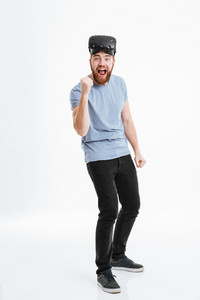 Young happy bearded man wearing virtual reality device standing over white background and looking at camera while making winner gesture.