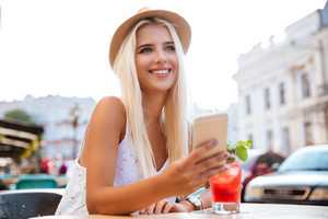 Young happy blonde woman in hat using smartphone while sitting at cafe outdoors