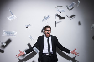 Young happy Business man in suit and glasses with falling money in studio. Isolated gray background