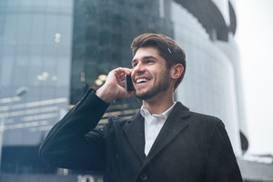 Young happy businessman dressed in official clothing standing near business center and look aside while talking by phone.