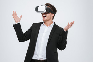 Young happy businessman standing at studio wearing 3d glasses virtual reality. Isolated over white background.