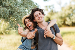 Young happy cheerful couple showing thumbs up and hugging over forest background