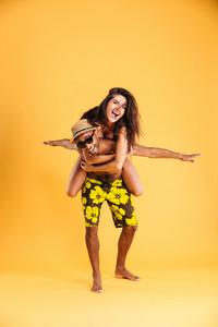 Young happy couple enjoying piggyback ride isolated on orange background