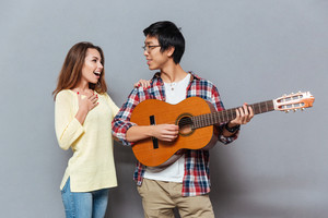 Young happy couple in love playing guitar isolated on the gray background