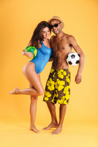 Young happy couple in swimsuits holding balls isolated on the orange background