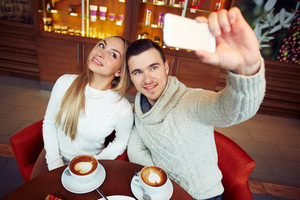 Young happy couple in warm sweaters taking their selfie in cafe