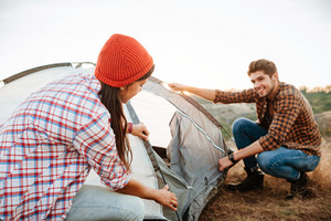 Young happy couple setting up a tent outdoors at sunset