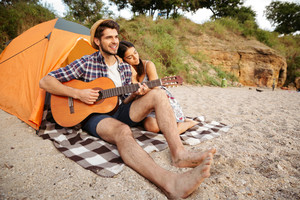 Young happy couple sitting at the tent and playing guitar at the beach