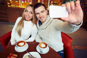 Young happy couple taking their selfie while sitting in cafe