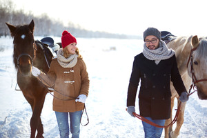 Young happy couple with horses walking in winter day