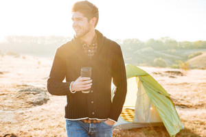 Young happy man drinking coffee outdoors with tent on the background