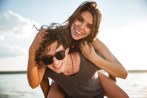 Young happy smiling couple in love piggyback at the beach