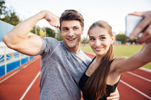 Young happy sports couple making selfie photo on stadium, man showing biceps on camera