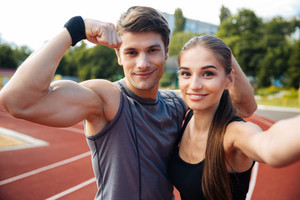 Young happy sports couple making selfie photo on stadium, man showing biceps