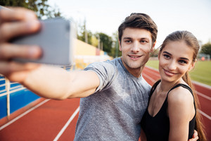 Young happy sports couple making selfie photo on stadium