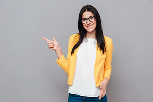Young happy woman wearing eyeglasses and dressed in yellow jacket pointing over grey background. Look at camera.