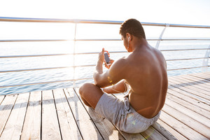 Young healthy afro american sports man resting after workout and listen music at the sea wooden pier