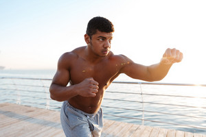Young healthy afro american sportsman doing boxing exercises at the pier outdoors