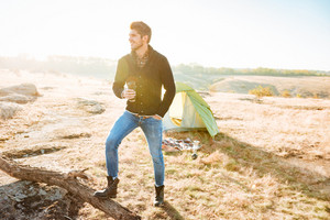Young hiking man drinking coffee outdoors with tent on the background