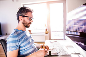 Young hipster architect working from home on computer, writing into personal organizer, taking notes