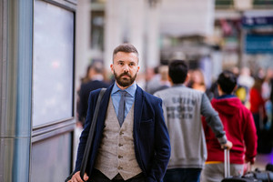 Young hipster businessman in blue suit at the station walking