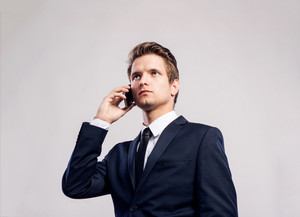 Young hipster businessman with smartphone making phone call. Studio shot on gray background.