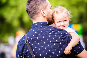 Young hipster father holding his little daughter in his arms, sunny summer day outside in park, rear view