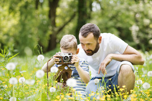 Young hipster father outdoors with his little son with camera, taking pictures of flowers. Sunny summer day.