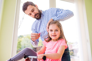 Young hipster father with his cute little daughter, styling her hair, riding bicycle indoors