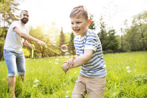 Young hipster father with little boy outside blowing bubbles, having fun, sunny summer day.