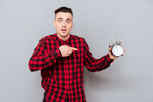 Young Hipster in red shirt holding clock in hand and pointing on them. Isolated gray background