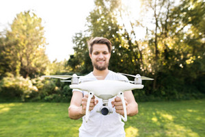 Young hipster man holding drone with camera. Green sunny nature.