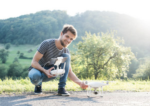 Young hipster man holding remote control and drone with camera. Green sunny nature.