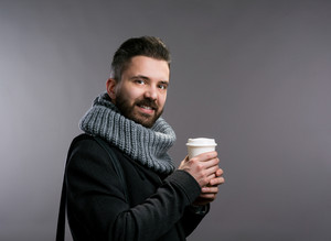 Young hipster man in black winter coat and knitted scarf holding a cup of coffee. Studio shot on gray background.