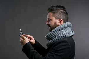 Young hipster man in black winter coat and knitted scarf holding a smartphone, texting. Studio shot on gray background.