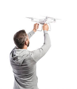 Young hipster man in gray sweatshirt holding drone with camera. Studio shot on white background, isolated. Rear view.