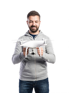 Young hipster man in gray sweatshirt holding drone with camera. Studio shot on white background, isolated.