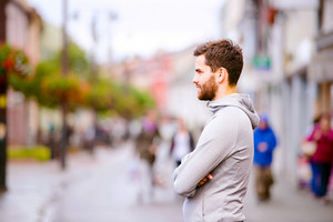 Young hipster man in gray sweatshirt running in town, resting, main street