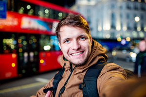 Young hipster man walking in the streets of London at night, taking selfie