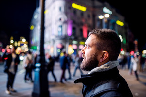 Young hipster man walking in the streets of London at night