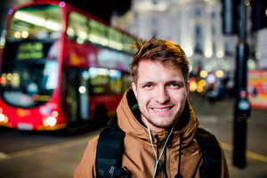 Young hipster man with earphones, listening music, walking in the streets of London at night