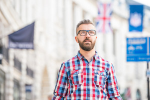 Young hipster man with eyeglasses in checked shirt shopping in the streets of London