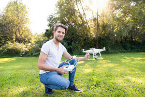 Young hipster man with remote control and drone with camera. Green sunny nature.