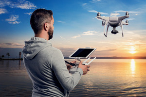 Young hipster man with remote control and flying drone with camera taking photos of beautiful sunset at the lake in Austria.