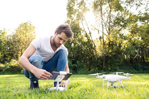Young hipster man with remote control with tablet and drone with camera. Green sunny nature.