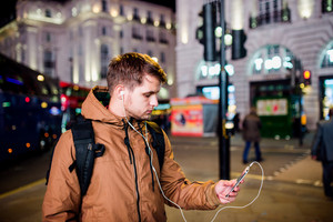 Young hipster man with smart phone, listening music, walking in the streets of London at night